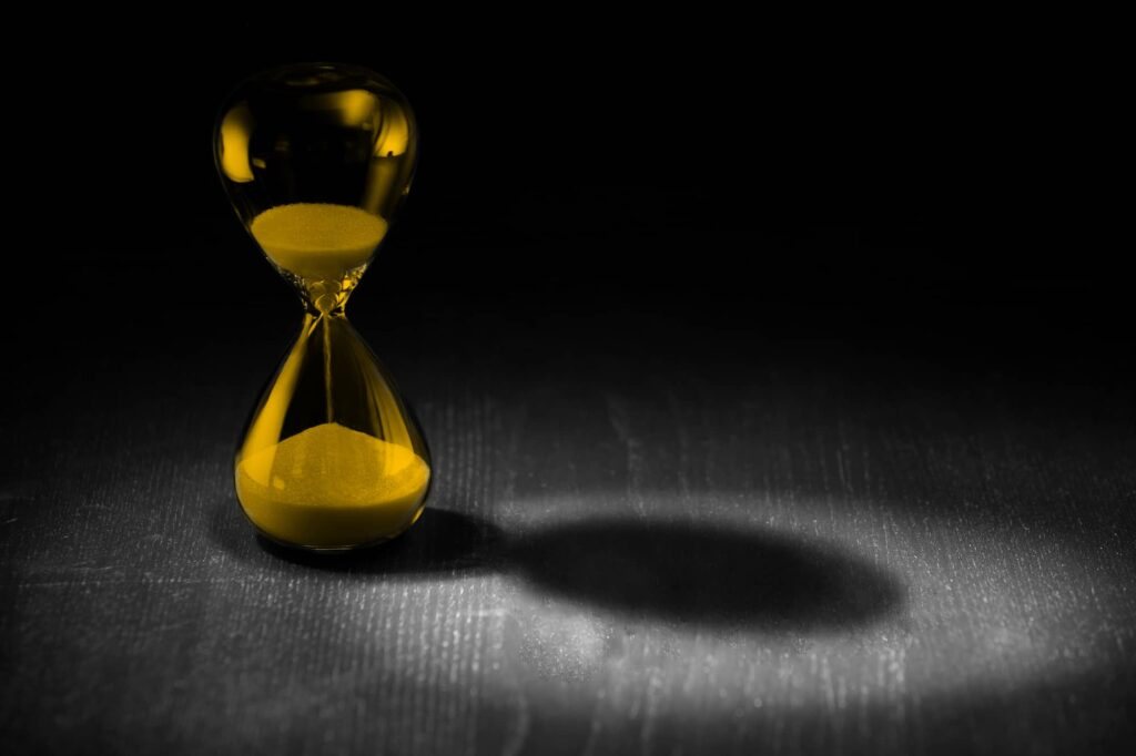 Investing header with yellow hour glass and shadow on dark table